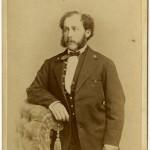 Albert Gihon standing near chair.